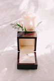Golden wedding ring in box and rose flowers on the side. Royalty Free Stock Image