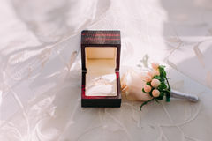 Golden wedding ring in box and rose flowers on the side. Royalty Free Stock Images