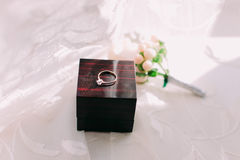Golden wedding ring in box and rose flowers on the side. Stock Photo