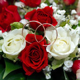 Golden wedding ring on the bride's bouquet. Bouquet of red and w Royalty Free Stock Photo