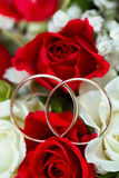 Golden wedding ring on the bride's bouquet. Bouquet of red and w Royalty Free Stock Image
