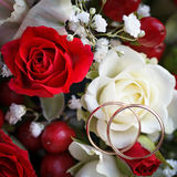 Golden wedding ring on bride's bouquet. Bouquet of red and w Stock Photos