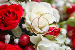 Golden wedding ring on bride's bouquet. Bouquet of red and w Stock Image