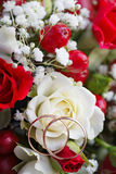 Golden wedding ring on  bride's bouquet. Bouquet of red and w Stock Images