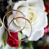 Golden wedding ring on  bride's bouquet. Bouquet of red and w Royalty Free Stock Photos