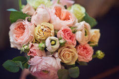 Golden wedding ring on the bride's bouquet. Bouquet of red and yelow roses Stock Photography