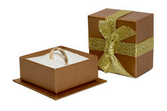 Golden wedding ring in open gift box isolated on white backgroun. Golden wedding ring in open gift box, box cover with ribbon and bow, isolated on white royalty free stock photography