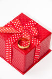 Golden wedding ring and red gift box with red bow Stock Images