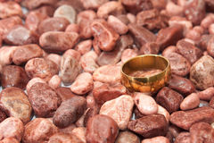Golden wedding ring on the red stones Royalty Free Stock Photo