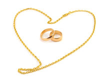 Golden wedding rings. With a chain composed of a heart on a white background Stock Photography