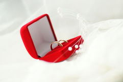 Golden wedding rings. Red jewelry box with gold wedding rings on a white cloth Royalty Free Stock Photography