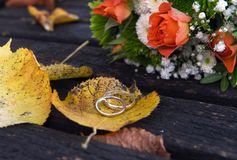 Golden wedding rings on a autumn leaf close-up. Golden wedding rings on a autumn leaf close-up with pink roses bouquet in the background Stock Images