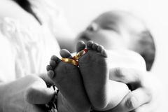 Golden wedding rings on baby's feet Royalty Free Stock Image