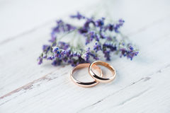 Golden wedding rings and beautiful small blue flowers on wooden tabletop Royalty Free Stock Image