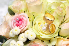 Golden wedding rings on the bouquet of roses Royalty Free Stock Photos