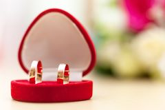 Golden wedding rings and bridal bouquet Stock Photos