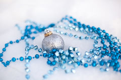 Golden wedding rings on Christmas ball and blue garland Stock Photography