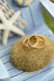Golden wedding rings on decorative white and blue toy chair with starfish Stock Photography