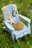 Golden wedding rings on decorative white and blue toy chair with starfish. And decorative fishing net in the background of green grass Royalty Free Stock Image