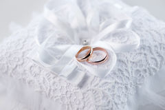 Golden wedding rings on decorative white lace pillow Royalty Free Stock Photo