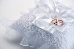 Golden wedding rings on decorative white lace pillow Royalty Free Stock Photos