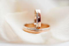 Golden wedding rings with diamonds lie on silk fabric Royalty Free Stock Images