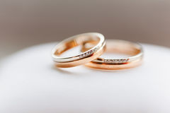 Golden wedding rings with diamonds on white background. Stock Photo