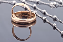 Golden wedding rings and elegant silver chain Stock Photo