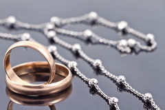 Golden wedding rings and elegant silver chain Stock Photography