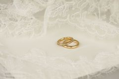 Golden wedding rings with embroidered lace. Golden wedding rings on a white envelope with ivory embroidered lace Royalty Free Stock Photos