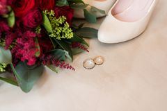 Golden wedding rings in focus on beige background with bridal shoes and flowers out of focus. Rings Stock Photos