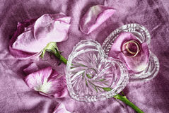 Golden wedding rings in a glass box in the form of heart and pink roses petals. Wedding background stock photo