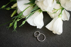 Golden wedding rings on grey background with white flowers Royalty Free Stock Images