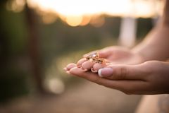 Closeup golden wedding rings in hands of woman and bride Royalty Free Stock Photos