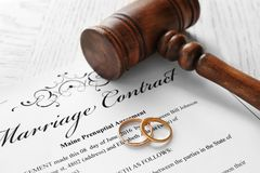 Golden wedding rings with judge gavel on marriage contract. Closeup Royalty Free Stock Photos