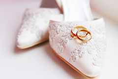 Golden wedding rings on lace silk fabric shoes. Stock Photo