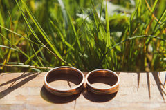 Golden wedding rings laying on wooden table Royalty Free Stock Photography