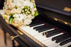 Golden wedding rings lie on the piano stock photos