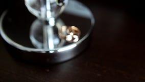 Golden wedding rings on metal surface in rack focus stock footage