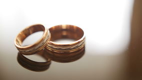 Golden wedding rings on mirror glasses table - one lies top of another stock video footage