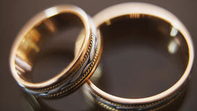 Golden wedding rings on mirror glasses table - one lies top of another, horizontal, macro. Golden wedding rings on mirror glasses table - one lies on top of Royalty Free Stock Photos