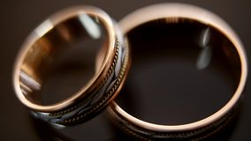 Golden wedding rings on mirror glasses table - one lies top of another, macro stock video footage