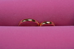 Golden wedding rings on pink background, close up Stock Images