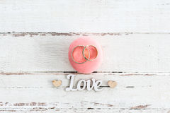 Golden wedding rings on pink macaron and love symbol with hearts Royalty Free Stock Images