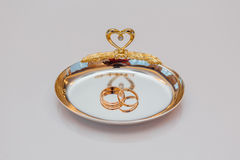 Golden wedding rings on a plate Royalty Free Stock Photos