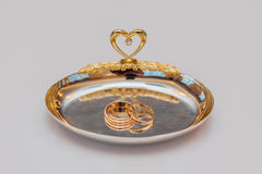 Golden wedding rings on a plate Royalty Free Stock Photography