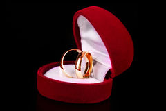Golden wedding rings in red box. Isolated on black royalty free stock photography