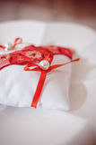 Golden wedding rings on red crimson and white ring pillow with Stock Images