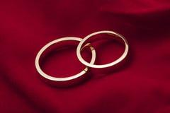 Golden wedding rings on red velvet Stock Images