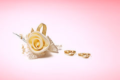 Golden wedding rings and rose on white background Stock Photography